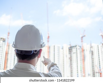 Engineer man back view wearing white hard safety helmet and white shirt pointing his right hand on construction building background on sunshine day.