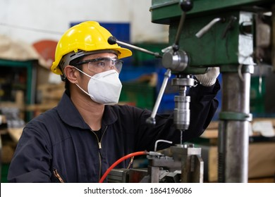 engineer man or factory worker wearing face mask for protect virus, using the machine in factory