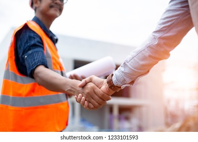 Engineer man handshake with asian business after finishing up meeting, partnership, teamwork, community, connection industriall and investment concept
