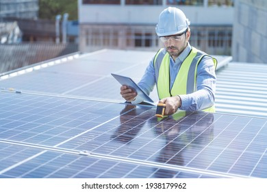engineer man inspects construction of solar cell panel or photovoltaic cell by electronic device. Industrial Renewable energy of green power. factory worker working on tower roof.