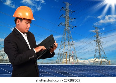 Engineer man with solar panel against high voltage towers background.