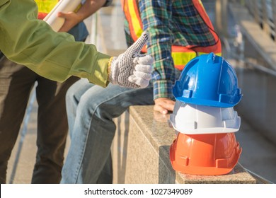 Engineer man Standing beside hat. He is show hand show good for work. He wearing green work clothes and a  Engineer man sitting. Photo concept work and engineer.