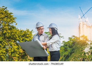 Engineer man and woman on outdoors landscape location construction site for check out the new project with blueprint, Save environment project, New project engineer outside trip