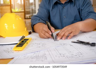 Engineer man working with drawings inspection in workplace in office .Engineering tools and construction concept. architect and Business concept.