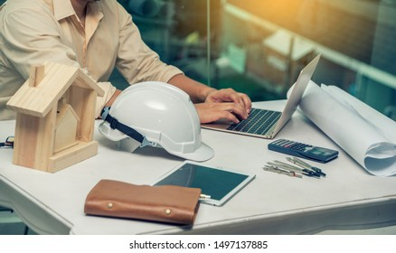 Engineer man working with laptop and blueprints,engineer inspection in construction site for architectural plan,sketching or design  a construction project ,Business concept