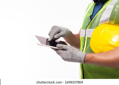 Engineer man working on digital tablet computer at worksite or industry. Handsome young industrial worker hold hard hat, safety glove, reflective vest. Blue collar worker plan project by use tablet