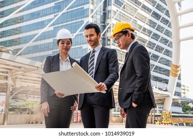 Engineer  Manager , Businessman and woman secretary Meeting  working Team building  holding Blueprint outdoors in construction site