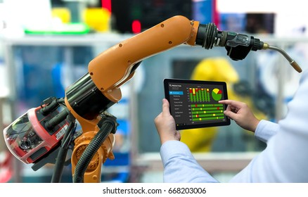 Engineer manager hand using tablet, heavy automation robot arm machine in smart factory industrial with tablet real time monitoring production system. Industry 4th iot concept.