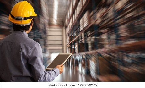 Engineer manager Wearing hard Hat using tablet check and control for workers with  warehouse logistics. Industry 4.0 concept.