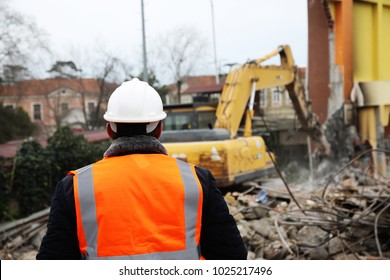Engineer mans in helmet and jacket controlling outdoor construction site. Engineerin demolition site.
