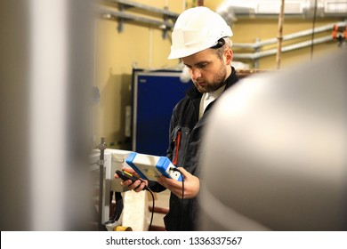 Engineer with measure tester on heat boiler. Worker make maintenance energy equipments on heating station