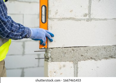Engineer measures the work out wall lightweight concrete blocks with a level at construction site.