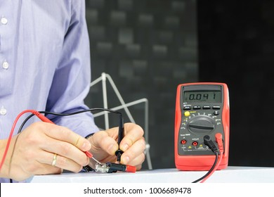 Engineer measuring with a multimeter in a laboratory