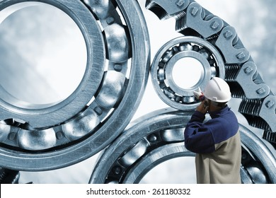 engineer, mechanic pointing at giant ball-bearings powered by chain,