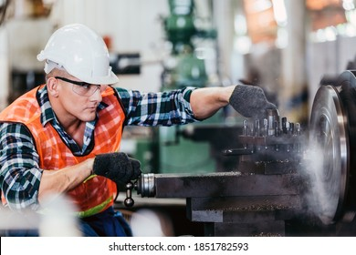 Engineer metalworker industrial experienced operator technician worker in safety hard helmet working on lathe machine, professional man in industry technology manufacturing factory workplace