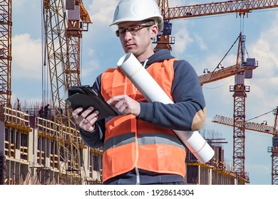 Engineer next to building cranes. Lots of construction cranes next to building. Concept - large construction project. Architect directs the construction process. Drawings and tablet in the hands.