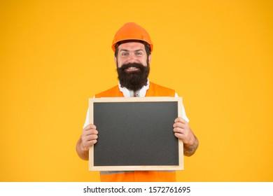Engineer occupation. Repairman engineer hold blackboard copy space. Installation of electrical equipment. Handsome repairman. Man bearded repairman builder work clothes. Responsibility and garanties.
