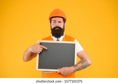Engineer occupation. Repairman engineer hold blackboard copy space. Man bearded repairman builder work clothes. Responsibility and garanties. Installation of electrical equipment. Handsome repairman.