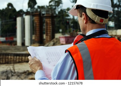 Engineer on the construction site looking at the plans, wearing white safety helmet and reflective vest