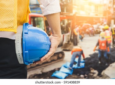 Engineer orders for workers to work safely at construction site, workers put  asphalt on the road