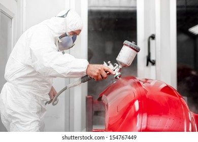 Engineer painting a red part of car with spray gun in special booth