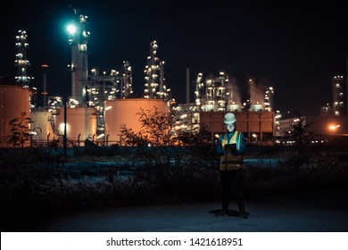 Engineer Petrochemical Asian man work late and hard with Smart tablet Inside the Refinery - oil and gas Industry Factory at night