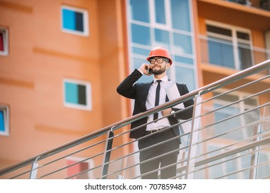 Engineer with plan in his hand talking on cell phone on construction building side.