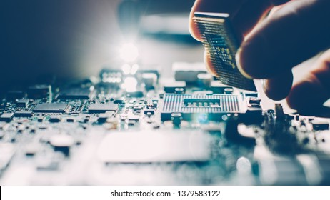 Engineer plugging CPU microprocessor to motherboard socket. Computer technology and hardware maintenance or repair.