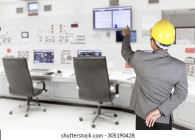Engineer pointing at monitor screen for command working at control room of a modern thermal power plant