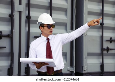 Engineer is pointing at site work. He is standing near the container.