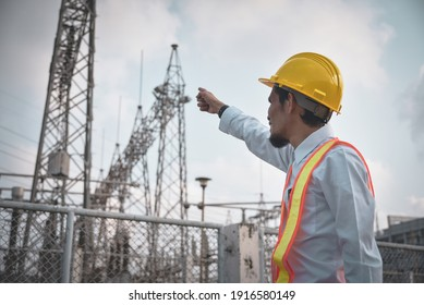 Engineer points to high voltage substation against cloudy sky background