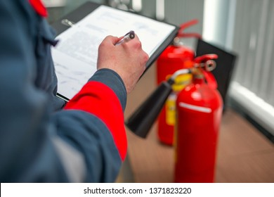 Engineer Professional are Checking A Fire Extinguisher Using Clipboard or checking Industrial fire control system,Fire Alarm controller, Fire notifier.System ready In the event of a fire.