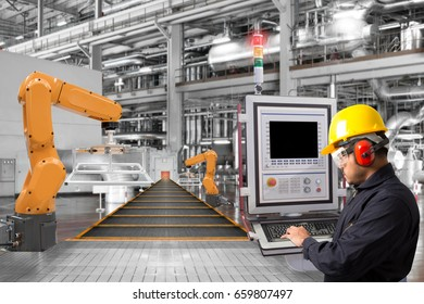 Engineer programming control robotic arms automation and conveyor belt in the factory