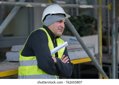 Engineer with protective workwear freezing outdoors