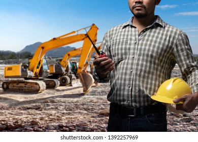 Engineer with radio communication in action during working with group heavy machinery prepare for work at construction site