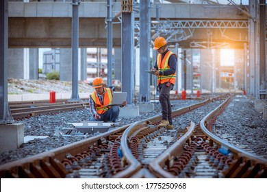 Engineer railway under inspection and checking construction railway switch and checking work on railroad station by laptop.Engineer wearing safety uniform and safety helmet in work.