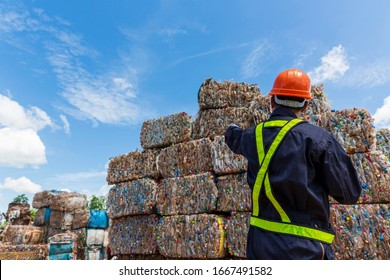 Engineer and Recyclable material. An engineer looking at recycling waste To proceed to the next process. Foreman wearing protective equipments and holding tablet and looking at Recyclable material.