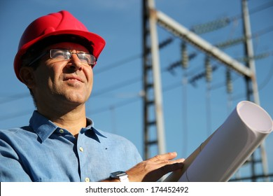 Engineer With Red Hard Hat and Blueprint Under the Power Lines.Engineer holding blueprints at an electrical substation.