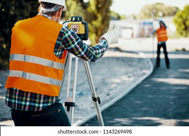 Engineer in reflective vest using equipment during geodetic work. Blurred colleague in the background