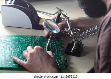 Engineer is repair circuit board with soldering iron and loupe