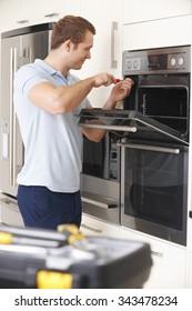 Engineer Repairing Domestic Oven In Kitchen