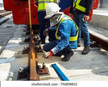 An Engineer with safety helmet and safety jacket checking rail alignment by using a flat sheet metal in the afternoon. weld visual and inspection. railway Track work.