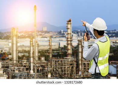 Engineer with safety helmet with oil refinery industry plant background
