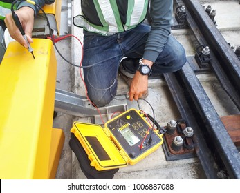 An Engineer with safety jacket checking conductor rail cover electrical resistance test by using a ohmmeter in the afternoon. weld visual and inspection. railway Track work.
