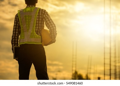 Engineer or Safety officer holding hard hat  in construction site.