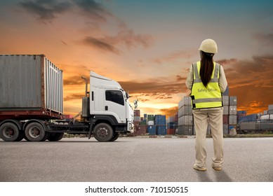 The engineer or safety officer working with container Cargo freight ship in shipyard at dusk for Logistic Import Export nature sunset background