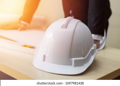 Engineer safety white helmet on work table and manager looking in blueprint for planing project,Business and Architect Concept