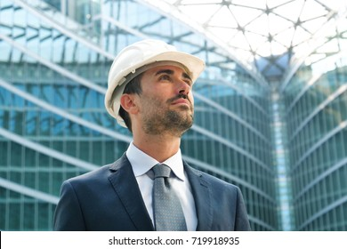 An engineer with a security helmsman, looks proud of the success of his construction project. Concept of: engineering, buildings, business, dream, success