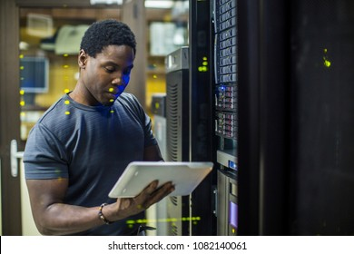 Engineer in the server room checking tablet