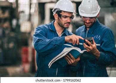 Techniker-Service-Team, das sich das Handbuch für Maschinenbedienung ansieht, arbeitet als Teamwork in der Fabrik zusammen.